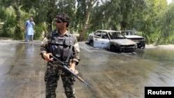 Pripadnik avganistanskih bezbednosnih snaga stražari na mestu napada u Jalalabadu, Avganistan, 10. jula 2018.