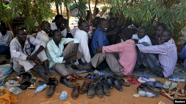 Internally displaced men sit inside a United Nations Missions in Sudan (UNMISS) compound in Juba December 19, 2013.