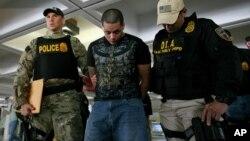 Agentes de la DEA llevan esposado a uno de los arrestados en el aeropuerto de San Juan, Puerto Rico.