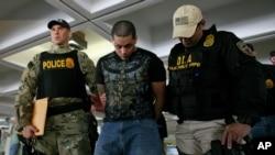Polisi unit anti-narkoba menahan seorang tersangka penyelundupan narkoba di bandar udara San Juan, Puerto Rico. (Foto: Dok)