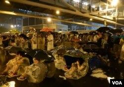 佔領中環行動進行期間下起傾盆大雨,無阻示威群眾,手持雨傘坐在馬路上繼續表達訴求。(美國之音湯惠芸攝)