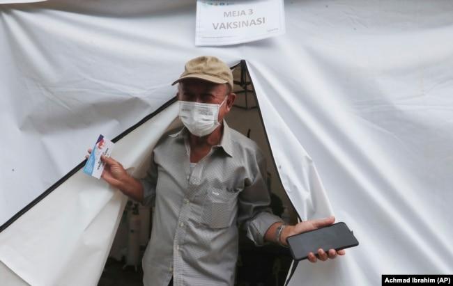 Erri Suprijadi berusia 70 tahun meninggalkan tenda setelah menerima suntikan vaksin COVID-19 di sebuah puskesmas di Jakarta, 8 Februari 2021. (Foto: Achmad Ibrahim/AP)