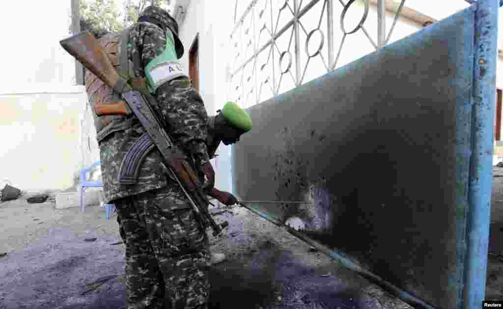 Askari ka tirsan AMISOM oo qiimaynaya burburkii ka dhashay weerarkii madaxtooyada, Mogadishu, July 9, 2014.