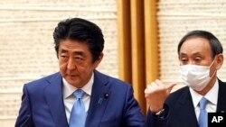 Perdana Menteri Jepang Shinzo Abe, kiri, memberi isyarat saat Kepala Sekretaris Kabinet Yoshihide Suga melihat pada akhir konferensi pers di kantor Abe di Tokyo pada hari Senin, 4 Mei 2020. (Foto: AP)