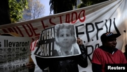 "Demonstrator covers face with poster reading ""Pena Out"" during protest in support of 43 missing students outside office of Mexico's Attorney General, Mexico City, Nov. 27, 2014."
