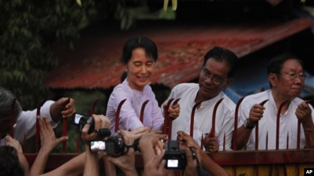Hands reach to touch the hand of Burma's pro-democracy leader Aung San Suu Kyi after her release from house arrest in Rangoon, 13 Nov 2010