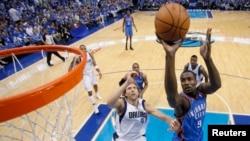 Dirk Nowitzki des Dallas Mavericks tente de bloquer Serge Ibaka d' Oklahoma City Thunder (9) devant le panier, Texas, 7 mai 2011.