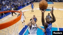 Serge Ibaka d' Oklahoma City Thunder (9) amorce une attaque vers le panier face à Dirk Nowitzki de Dallas Mavericks (41) lors d'un match de la NBA à Dallas, Texas, 7 mai 2011.
