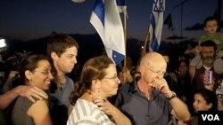 Noam and Aviv Shalit (kanan), orang tua prajurit Israel Gilad Shalit, berkumpul bersama tetangga dan kerabatnya di Mitzpe Hila, Israel utara mendengarkan berita rencana pembebasan Gilad Shalit (12/10).