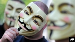 "FILE - Activists of the international network ""Anonymous"" pose with Guy Fawkes masks in an undated photo in Berlin, Germany. The group has declared ""total war"" against US presidential hopeful Donald Trump."