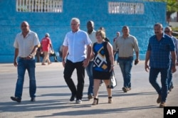 Cuba's Vice President Miguel Diaz-Canel and his wife Lis Cuesta Peraza walk, surrounded by security, to a voting center during elections for national and provincial representatives for the National Assembly in Santa Clara, Cuba, Sunday, March 11, 2018. (AP Photo)