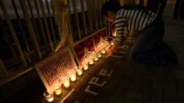 A protester arranges candles during a candlelight vigil outside a China Liaison Office in Hong Kong, February 13, 2013.