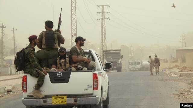 Armed Shi'ite volunteers, travel in a vehicle before taking their positions during a patrol after clashes with militants of the Islamic State, formerly known as the Islamic State in Iraq and the Levant on the outskirts of Samarra in Salahuddin province, July 13, 2014.