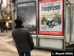 A Parisian looks at a newspaper billboard on France's current political dilemmas.