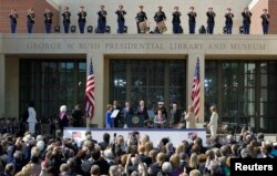 FILE - (L-R) U.S. First lady Michelle Obama, former first lady Barbara Bush, former first lady Laura Bush, President Barack Obama, former President George W. Bush, former President Bill Clitnon, former President George H.W. Bush, former President Jimmy Carter, former first lady Hillary Clinton, and former first lady Rosalynn Carter arrive at the dedication for the George W. Bush Presidential Center on the campus of Southern Methodist University in Dallas, Texas, April 25, 2013.