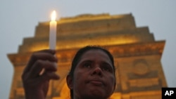 A mourner attends a candlelight prayer ceremony for nun Valsha John at the India Gate in New Delhi, November 22, 2011. John, 52, was beaten and hacked with an axe by unknown assailants in India's eastern Jharkhand state where she had led a campaign for fi