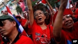 Thai anti-government 'red shirt' protesters react as their leader addresses them at Bangkok's shopping district, 19 Dec 2010