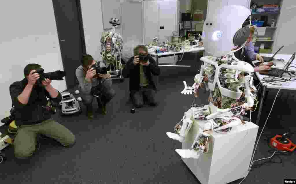 摄影师在瑞士苏黎世的苏黎世大学的人工实验室的一个新闻发表会上为一个呈现人形的机器人ROBOY 拍照。
