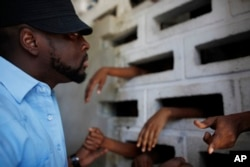 Haitian musician Wyclef Jean speaks to inmates at the women's annex of the National Prison in Port-au-Prince, June 16, 2010.