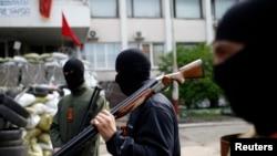 手持武器的親俄羅斯武裝分子在5月4日在東部港口城市馬里烏波爾市政廳前守衛。