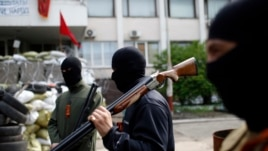 Armed pro-Russian rebels stand guard outside the town hall in Mariupol, eastern Ukraine, May 4, 2014.