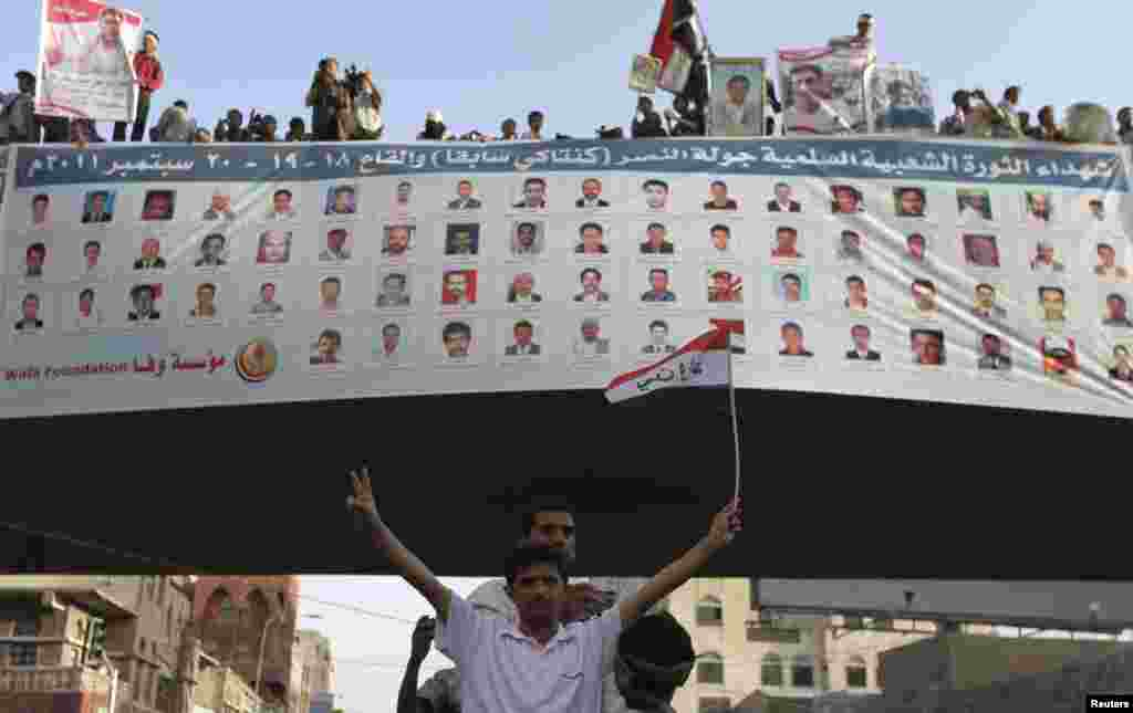 A man poses with the victory sign in front of victims' pictures, at a rally in Sanaa September 18, 2012, commemorating people killed during last year's unrest against former Yemeni president Ali Abdullah Saleh. Tuesday marked the first anniversary of a ma