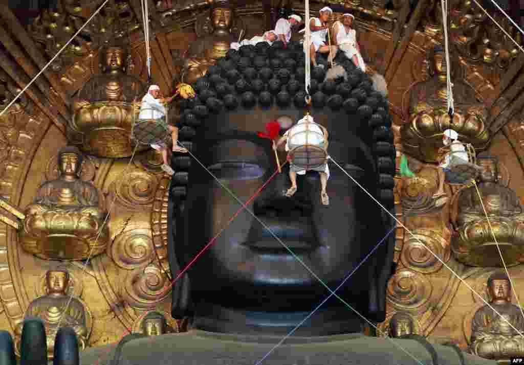 Pendeta Budha dan relawan membersihkan patung Buddha setinggi15-meterdi Kuil Todaiji, Nara, Jepang.