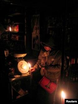 资料照:中国湖南郴州的一个小店里的商贩在蜡烛光里卖东西。