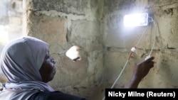 Seorang perempuan sedang memasang lampu surya sebagai ilustrasi. (Foto: Reuters/Nicky Milne)