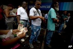 A woman counts her 100-bolivar notes while standing in line outside a bank in Caracas, Venezuela, Tuesday, Dec. 13, 2016.