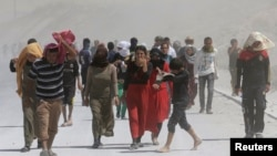 Displaced people from the minority Yazidi sect march in a rally at the Iraqi-Turkish border crossing in Zakho district of the Dohuk Governorate of the Iraqi Kurdistan province August 17, 2014.