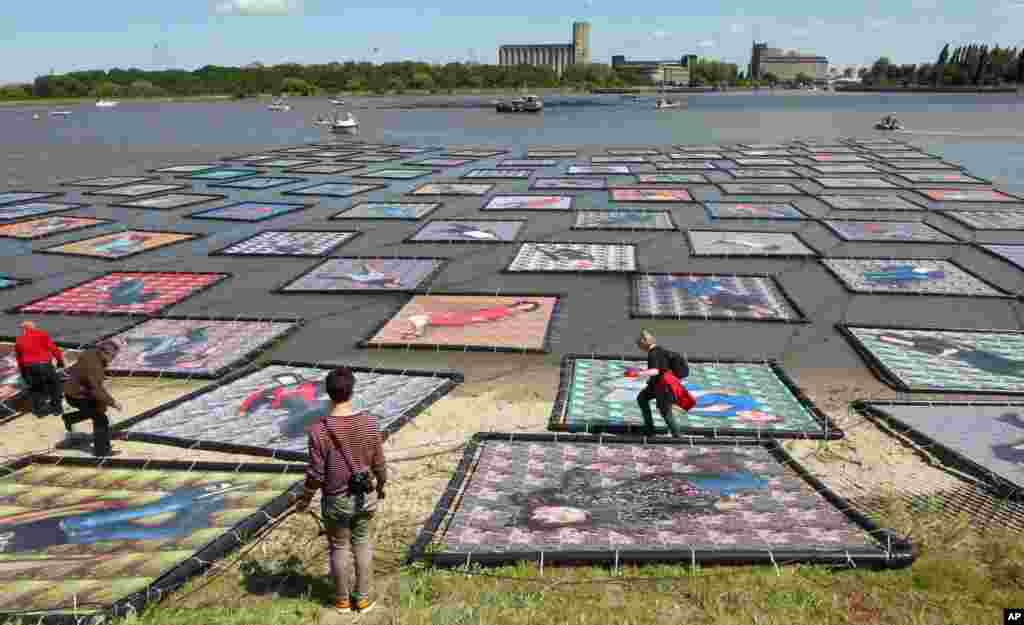 "People look at floating portraits of ""We Drift"" by Belgian artist Wim Tellier on the Scheldt river in Antwerp, Belgium."