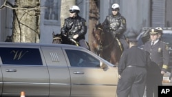 A funeral home limousine passes policemen near the New Hope Baptist Church in Newark, New Jersey, February 18, 2012.