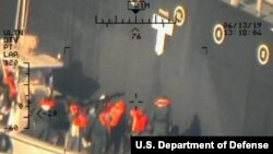 This image released by the Pentagon June 17, 2019, and taken from a U.S. Navy helicopter, shows what the Navy says are members of the Islamic Revolutionary Guard Corps Navy removing an unexploded limpet mine from the M/T Kokuka Courageous.
