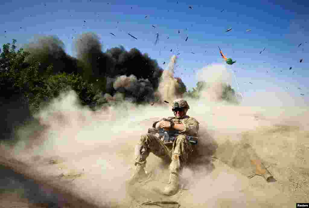 May 31: Jake Beaudoin, a U.S. Army Private, takes cover during a controlled detonation in Kandahar province, southern Afghanistan.