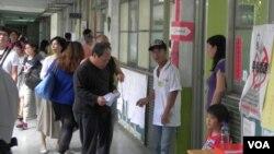 选民在台北一处投票站排队等候投票