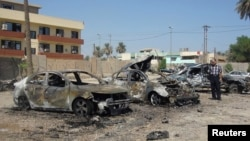A man looks at damaged vehicles at the site of a car bomb attack in Baghdad's Kadhimiya district, September 30, 2013.