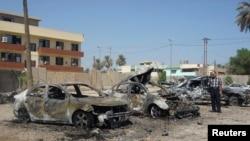 Seorang pria mengamati mobil-mobil yang hancur akibat serangan bom di distrik Kadhimiya, Baghdad (30/9).