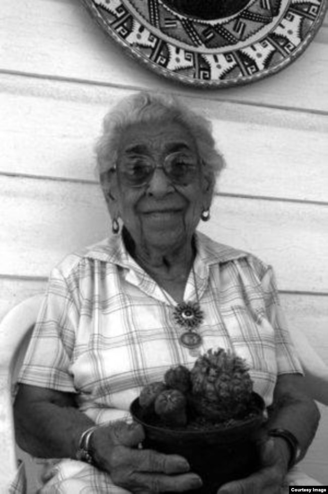 Amada Cardenas, holding a basket of peyote, outside of her home in Mirando City, Texas, 1994.