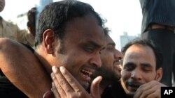 کراچی میں پانچ فروری کو ایک بس پر موٹر سائیکل بم حملے کے بعد ایک شخص ماتم کر رہا ہے