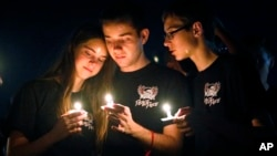 Attendees comfort each other at a candlelight vigil for the victims of the shooting at Marjory Stoneman Douglas High School, Feb. 15, 2018, in Parkland, Fla.