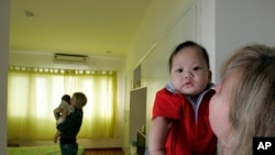 越南河内: 加利福尼亚州的莫妮卡(右)抱着从越南领养的7个月大的宝宝; 她的室友,来自弗吉尼亚州的特雷西·萨姆纳(左),抱着5个月大的越南婴儿