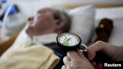 A nurse checks the pressure in the trachea of an 83 year-old man in a permanent vegetative state, at an intensive care nursing home in Germany, April 12, 2011. The patient has been in this condition since suffering a stroke. REUTERS