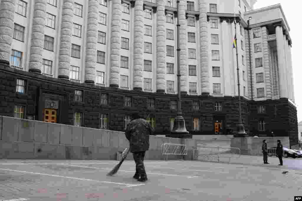 Дворник с метлой возле Дома правительства после митинга ликвидаторов Чернобыльской катастрофы