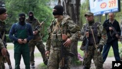 Pasukan separatis pro-Rusia siaga di balik barikade di komplek gedung pemerintah di kota Slovyansk, Ukraina timur, Jumat (2/5).