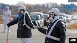 Cảnh sát Nhật hướng dẫn người di tản khỏi khu vực nhà máy điện hạt nhân Fukushima Daiichi sau vụ nổ ở thị trấn Tomioka thuộc Quận Fukushima, ngày 12 tháng 3, 2011