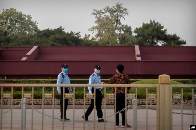 Oficiales de policía chinos usando mascarillas para impedir la propagación del coronavirus hablan con una persona cerca de la Plaza de Tiananmen en Beijing, el 29 de abril de 2020.