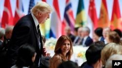 El presidente Donald Trump conversa brevemente con Juliana Awada, la esposa del presidente argentino Mauricio Macri, en la cena en la que también conversó con Putin en Hamburgo.