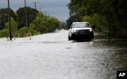 지난해 8월 허리케인 '하비'가 몰고온 폭우로 미국 루이지애나주 로와시의 도로가 침수된 가운데 빗길 위에서 트럭이 전전긍긍하고 있다.