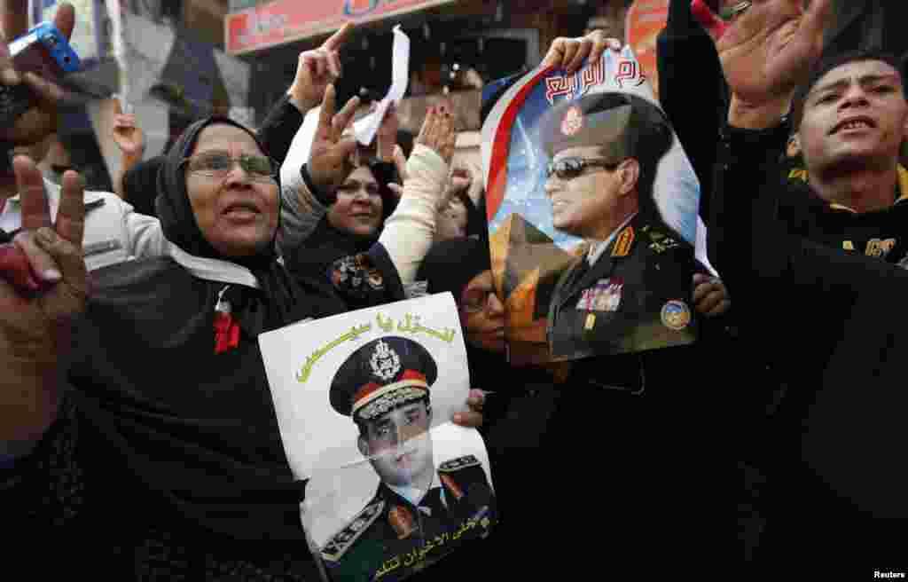 14일 이집트 카이로 북부 임바바의 법원 건물에서 폭탄 테러가 발생한 가운데, 파타 엘시시 국방장관의 지지자들이 구호를 외치고 있다.